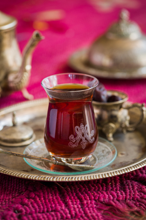 oriental rug: Tea set in oriental style in pear shaped glass with spoon and vintage kettle and dates fruit on silver tray on pink old rug Stock Photo