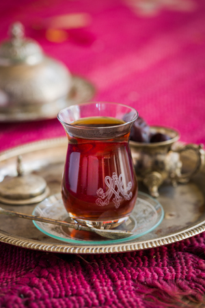 Tea set in oriental style in pear shaped glass with spoon and vintage kettle and dates fruit on silver tray on pink old rug Stock Photo
