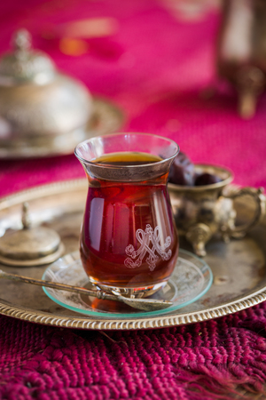 oriental rug: Tea set in oriental style in pear shaped glass with spoon and vintage kettle and dates fruit on silver tray Stock Photo