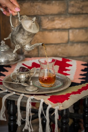 oriental rug: Tea set in oriental style in pear shaped glass with spoon and vintage kettle poring tea with dates fruit on silver tray on ethnic style rug with tassels. Stock Photo