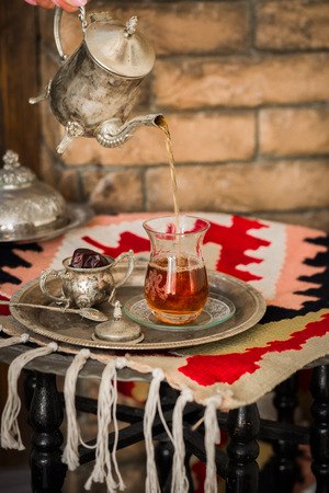 Tea set in oriental style in pear shaped glass with spoon and vintage kettle poring tea with dates fruit on silver tray on ethnic style rug with tassels. Stock Photo