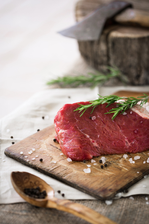 Raw beef slices on wooden cutting board sprinkled with sea salt and peppercorn and rosemary leaves with wooden stub with cleaver by side on burlap table cloth Stock Photo