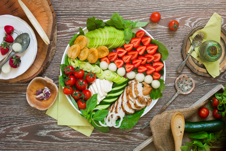onion rings: Warm grilled chicken salad with strawberries, melon balls, onion rings, tomatoes, mangold, peas, white cheese, cucumber, avocado, basil leaves in white oval plate on wooden table with fork and spoon Stock Photo