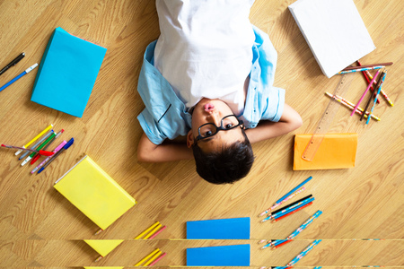 Smart preschool boy in blue shirt with eye glasses smiling, sitting on the floor with colorful books and pens, looking to the camera, home schooling and back to school, wunderkind concept