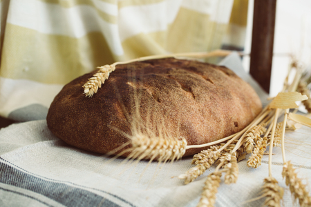 Organic sour dough loaf of bread with golden yellow sprouted wheat grains and spikes on table cloth, rural almosphere