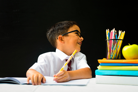 Cute smart handsome school boy in white shirt with eye glasses, writing at the desk in classroom, distracted, talking happy first grader pupil, smiling, knowledge study black board in the background,