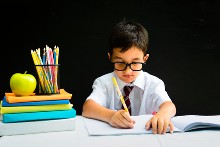 Cute smart handsome school boy in white shirt with eye glasses, writing at the desk in classroom, happy first grader pupil, smiling, knowledge study black board in the background, back to school conce 写真素材