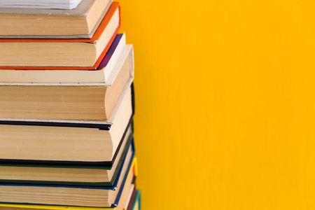 Stack of old books isolated on yellow background, vintage library, education back to school concept