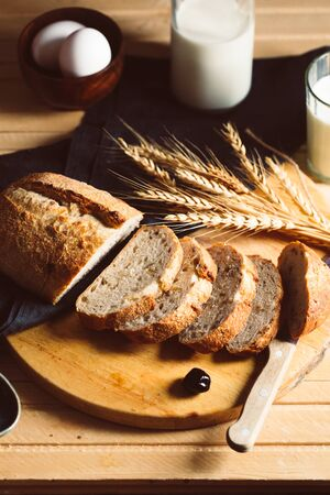 Slices of home made organic bread on wooden cutting board with wheat spikes. Rural scene, rustic style, copy space