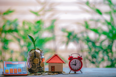 House Placed On Coins. Notebook and Pen Prepare Planning Savings Money of Coins to Buy a Home Concept For Property Ladder, Mortgage And Real Estate Investment. For Saving Or Investment For A House. Stock Photo