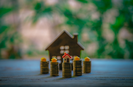 A small house on a pile of coins is used as an asset, financial concept for mortgage, financial investment fund and home loan, interest rate.