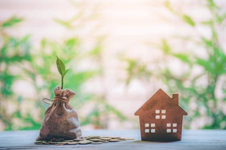 Klein huis voegt muntkolom toe Het concept van geld besparen, vastgoedbeleggingen