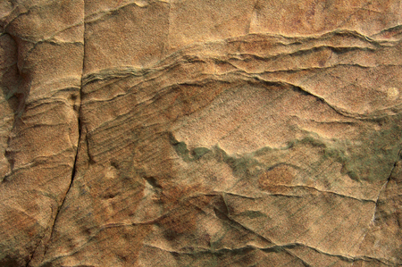 Wall, background, texture of nominated rock.Image of the surface of the surface of a rock in the foreground, cracked, chipped, deepening