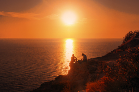 Climbing on the rocky coast of the Black Sea at sunset. Cape Fiolent, Crimean peninsula
