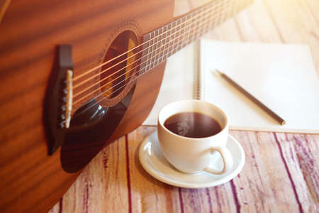 Acoustic guitar placed with a coffee cup