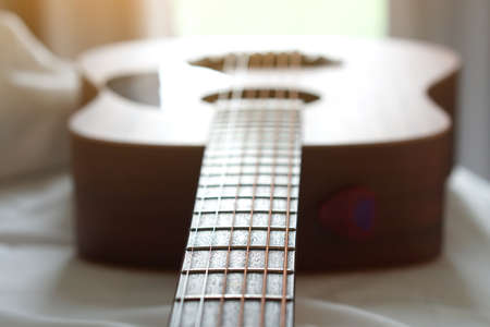 Acoustic guitar on white cloth background, Used to play music and notes, for sing a song, macro abstract.