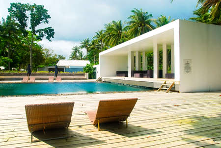 タイでのサンベッドとトロピカルなスイミング プール