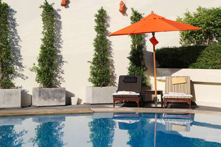 Lounge chairs with umbrella in a swimming pool invite you to relax  Stock Photo - 16531788