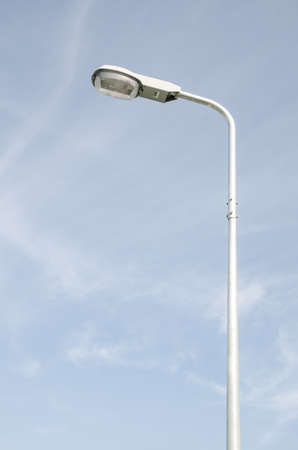 Street light with halogen lamp against blue sky photo