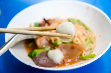 A pair of chopsticks holding a fish ball with a bowl of Thai Noodle Style  photo
