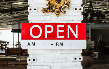 open sign hanging on a pole outside a restaurant, store, office or other Standard-Bild