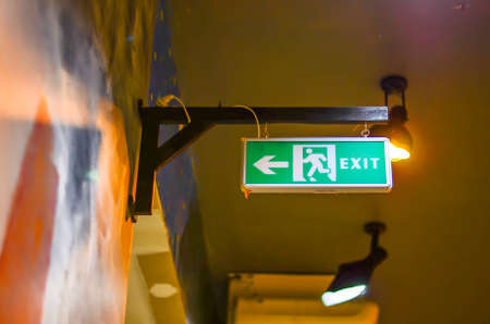 Illuminated green exit sign suspended from the ceiling in a public transportation facility  Signage consists of a human figure running and an arrow pointing at a door