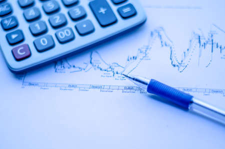 pen placed over financial statistics and charts with calculator
