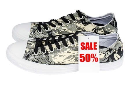 Sale sign made of paper promoting large discounts pattern soldier sneakers isolated on white background