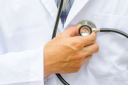 Close up male doctor is hand checking his own heart Standard-Bild