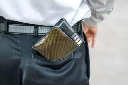 pickpocket: Closeup. Careless man with wallet falling back pocket. Risk of theft.