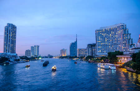 organized group: Bangkok cityscape with river and boat at night time . Chao Phraya river scene in Bangkok City, Thailand,cityscape , focus is building Stock Photo