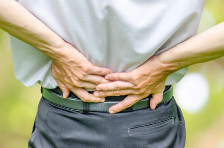 close up of a  man holding his back in pain