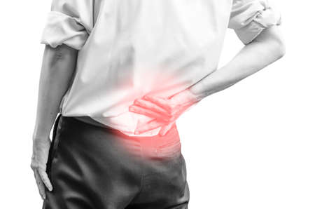 chiropractic: close up of a  man holding his back in pain, isolated on white background, monochrome photo with red as a symbol for the hardening