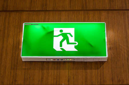 public figure: Illuminated green exit sign suspended from the ceiling in a public transportation facility. Signage consists of a human figure running
