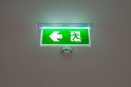 door casing: Illuminated green exit sign suspended from the ceiling in a public transportation facility. Signage consists of a human figure running and an arrow pointing at a door.