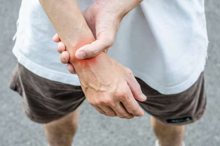 wrist pain: Wrist pain. Male holding hand to spot of wrist pain.