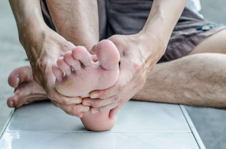 massage homme: La main de l'homme de se faire masser un pied Banque d'images