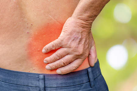 soreness: close up of a Senior man holding his back in pain, monochrome photo with red as a symbol for the hardening
