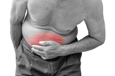 hardening: Senior man suffering from stomach ache because he has diarrhea ,monochrome photo with red as a symbol for the hardening Stock Photo