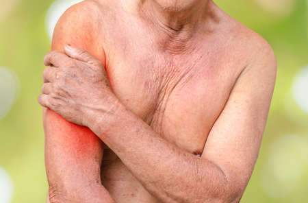 back rub: Senior man having shoulder pain,monochrome photo with red as a symbol for the hardening Stock Photo