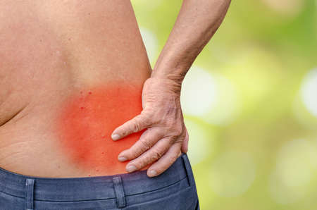 hardening: close up of a Senior man holding his back in pain, monochrome photo with red as a symbol for the hardening