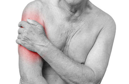 seniors suffering painful illness: Senior man having shoulder pain,monochrome photo with red as a symbol for the hardening Stock Photo