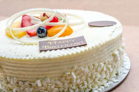 vanilla cake: vanilla cake and fruit with words happy birthday on it