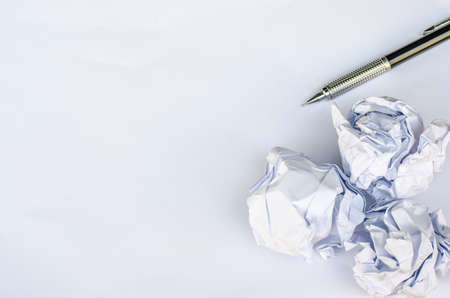 screwed: Writing concept - crumpled up paper wads with a sheet of white paper and pencil