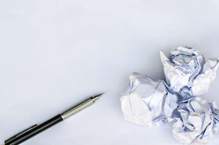 stress ball: Writing concept - crumpled up paper wads with a sheet of white paper and pencil