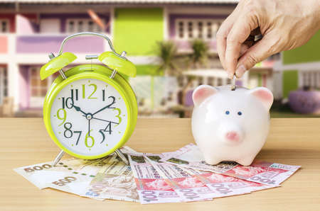 Piggy bank with money and alarm clock on wood table background ,hand add coin to piggy bank save coin, time and money concept on home background.
