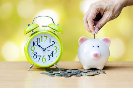 Piggy bank with coin and alarm clock on wood table background and alarm clock on wood table background ,hand add coin to piggy bank save coin, time and money concept.