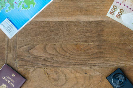 old photograph: Black compact camera and map and money and passport on wood table background Stock Photo