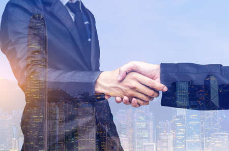 Double exposure of two businessmen shaking hands against white background