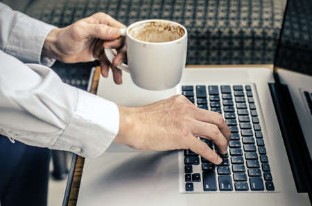 man with a cup of coffee working on his laptop Stock Photo